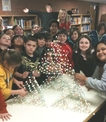 Albuquerque students assembling 256 tetrahedrons into a bigger copy of the same shape.